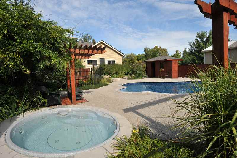 in-ground pool with vinyl liner and exposed aggregate pool decking