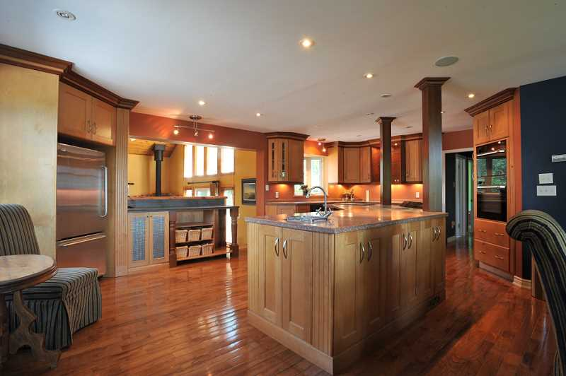 Maple Kitchen, w/ hardwood flooring, Corian counters, pot lights, huge centre island with bar sink, cook top and microwave