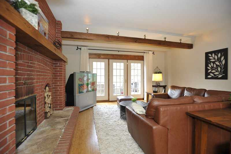 Family Room - bamboo flooring, a wood-burning fireplace, beamed ceiling & garden door walkout