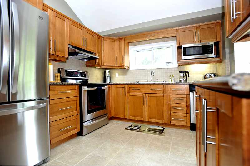 maple cabinetry, ceramic flooring and backsplash, stainless appliances, and vaulted ceiling