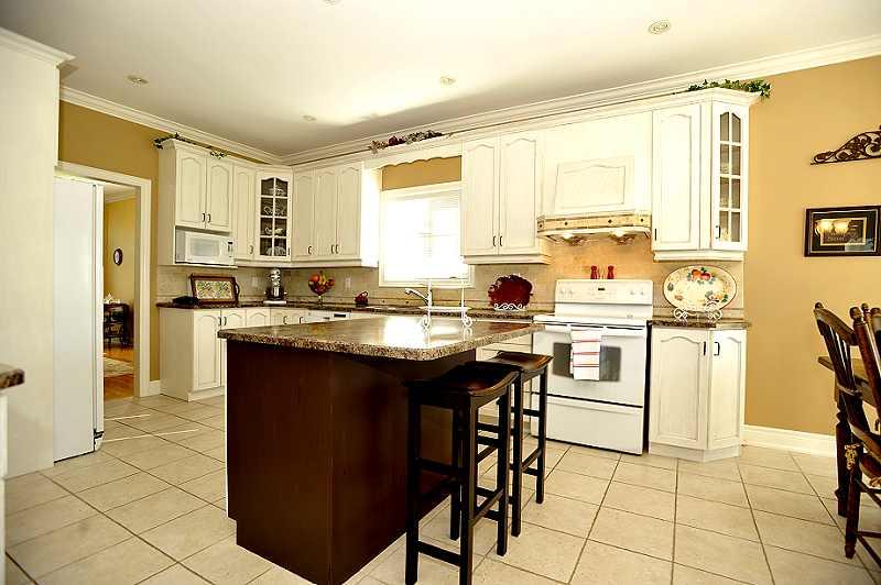 Kitchen has antiqued oak cabinetry, travertine backsplash, centre island, crown mouldings, ceramic flooring
