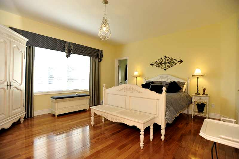 Master Bedroom with a double-door entry, hardwood flooring, walk-in closet, and a 5-piece ensuite