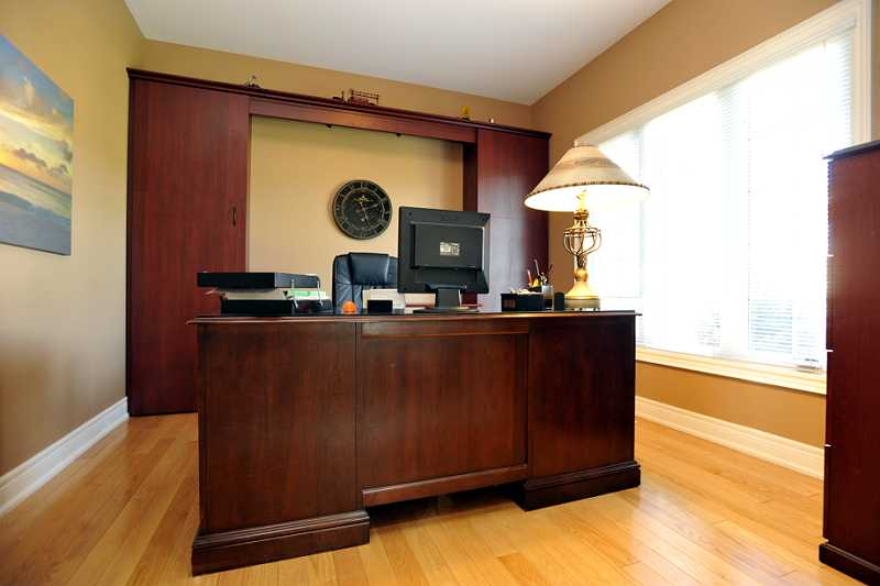 main floor Office has hardwood and a built-in wall cabinet with closet behind