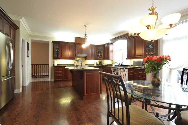 High-end cherry wood Kitchen has a centre island, granite counters