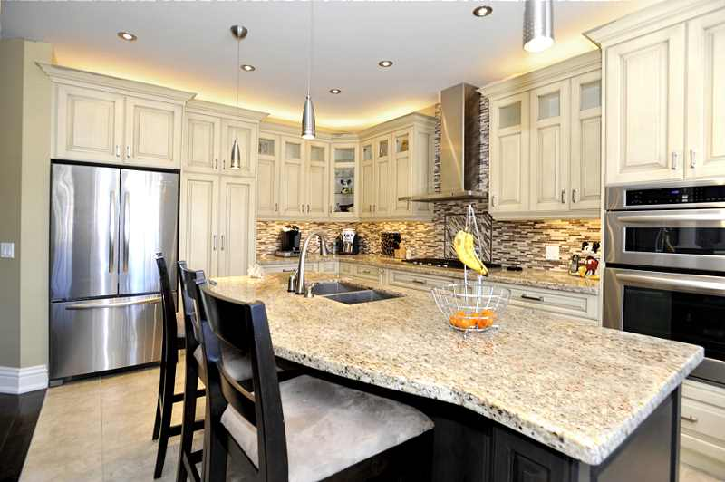 huge centre island with breakfast bar, pot lights, granite counters, ceramic floors & walk-out to the deck